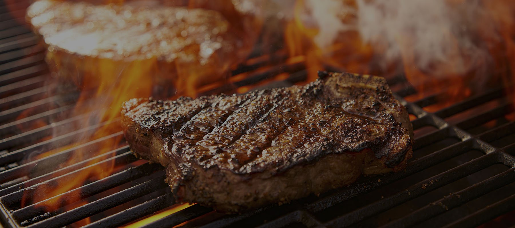 rib-eye steaks cooking on flaming grill