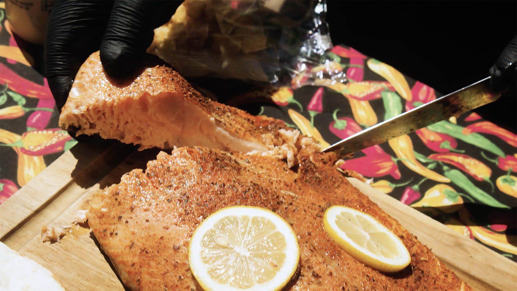 Grilled salmon with lemon slices being sliced on cutting board